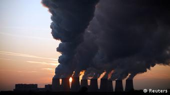 Backlit by a twighlit sky, plumes of dark steam or smoke rise from the chimneys of a silhouetted power plant. Photo: Pawel Kopczynski