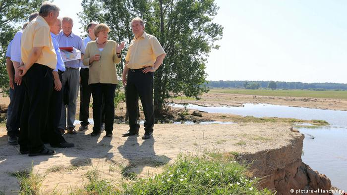 Chancellor Angela Merkel (center) on 23.07.2013 in Fischbeck (Saxony-Anhalt) standing next to State Premier Reiner Haseloff (right) at the point where a dam on the River Elbe broke. (Photo via Jens Wolf/dpa)