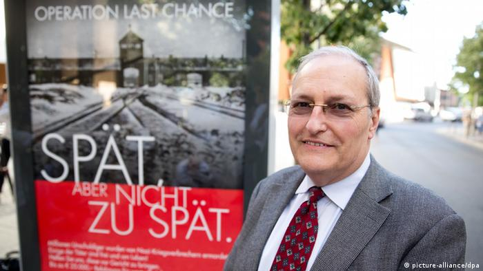 Efraim Zuroff, standing in front of one of the posters Photo: Jörg Carstensen/dpa pixel