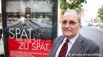 Efraim Zuroff in front one of the 'Late, but not too late' posters