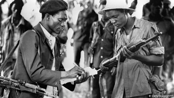 A guerilla reads his rifle serial number to a Patriotic Front Liberation officer