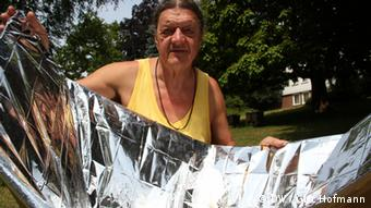 A man holds a funnel-shaped piece of cardboard covered in foil. It works as a solar cooker. (Foto: DW/Grit Hofmann)