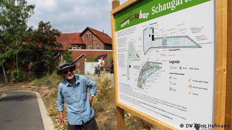 A man looks at a board that lists various display gardens (Foto: DW/Grit Hofmann)