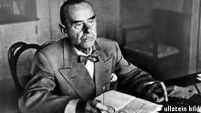 *06.06.1875-12.08.1955+ Schriftsteller; D / USA - sitzt mit einem Brief am Schreibtisch - ohne Jahr Brille in Hand Zigarre