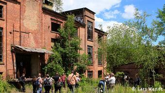 Totale der Papierfabrik mit einer Gruppe von geführten Fotografen