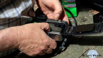 Detail von Händen, die einen Fotofilm in den Fotoapparat legen