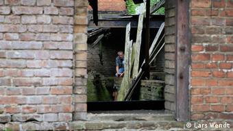 Blick durch eine Mauer ins zerfallene Innere der Fabrik
