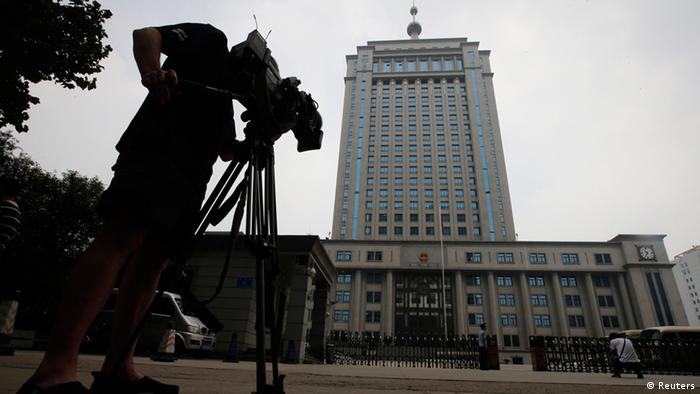 A television cameraman films the exterior of Jinan Municipality People's Intermediate Courthouse buildling, where the trial for disgraced Chinese politician Bo Xilai is likely to be held in Jinan, Shandong province, July 25, 2013. China has charged disgraced former senior politician Bo Xilai with bribery, abuse of power and corruption, state news agency Xinhua said on Thursday, paving the way for his trial.REUTERS/Kim Kyung-Hoon (CHINA - Tags: POLITICS CRIME LAW)
