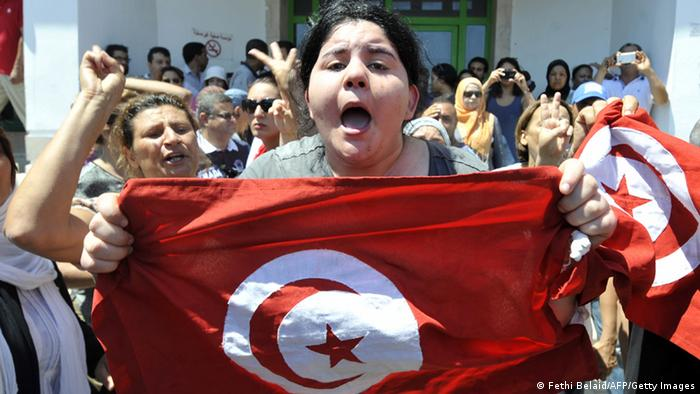 Belkaeis Brahimi, the daughter of Tunisian opposition politician Mohamed Brahmi, shows a national flag shouting outside a hospital after her father was killed on July 25, 2013 in Ariana, outside Tunis. Mohamed Brahmi, general coordinator of the Popular Movement and member of the National Constituent Assembly, was shot dead outside his home in Ariana, state media announced. AFP PHOTO / FETHI BELAID (Photo credit should read FETHI BELAID/AFP/Getty Images)