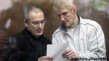 ARCHIV - Der ehemalige Generaldirektor des russischen Ölkonzerns Yukos, Michail Chodorkowski (l), spricht am 02.11.2010 im Khamovnichesky-Gericht in Moskau, Russland, mit seinem Ex-Geschäftspartner Platon Lebedew. Platon Lebedew kommt nicht früher aus dem Gefängnis frei. Lebedews Strafe von 13 Jahren Haft wegen Öldiebstahls und Steuerhinterziehung war erst vor gut einem Monat überraschend auf neun Jahre und acht Monate reduziert worden. Damit wäre der Ex-Manager bereits am 2. März 2013 freigekommen. Foto: EPA/SERGEI CHIRIKOV