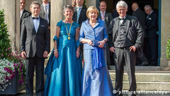 Angela Merkel arrives flanked by her husband and other guests in Bayreuth Photo: Tobias Hase/dpa