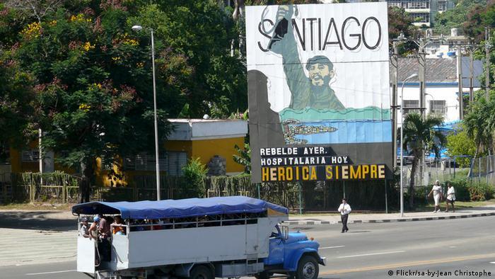 Ein großes Schild an einer Staße in Santiago der Cuba zeigt einen gemalten Fidel Castro mit hochgeregtem Gewehr. Der Schriftzug auf spanisch verkündet: Rebelde ayer, hospitalaria hoy, heróica siempre (deutsch: Gestern Rebellen, heute gastfreundlich, immer heroisch) (Foto: Flickr/sa-by-Jean Christophe)