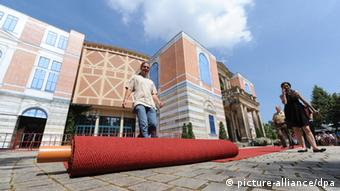 Workers roll out the red carpet for the opening of the Bayreuth Festival 2013 in Bayreuth, Germany, 25 July 2013. The one-month Wagner festival is Germany's most prestigious culture event. Photo: Daniel Karmann/ dpa
