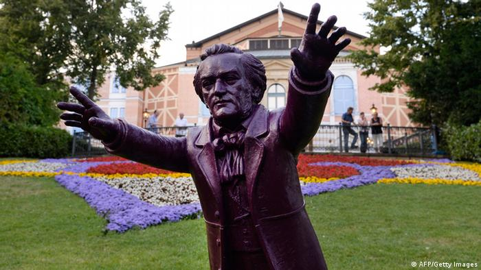 A figure of Richard Wagner by German artist Ottmar Hoerl can be seen in front of the opera house prior to the opening of the Bayreuth Wagner Opera Festival with the showing of 'The Flying Dutchman' in the southern German city of Bayreuth on July 25, 2013. This year, the month-long festival, for which the waiting list for tickets is 10 years and longer, is being opened by a revival of 'The Flying Dutchman' in a staging by German director Jan Philipp Gloger. AFP PHOTO / CHRISTOF STACHE (Photo credit should read CHRISTOF STACHE/AFP/Getty Images)