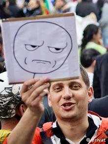 Kiril Todorov, systems administrator from Sofia, holding up a poster at a demonstration.