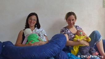 In Bonn, two mothers sit on the floor holding their babies at a diaper free workshop, given by Freya Donner