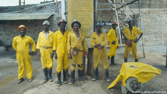 ZIMBABWE Industry Group of miners in safety helmets and work clothes at Patchway gold mine with Code of Signals mining regulations notice behind them.