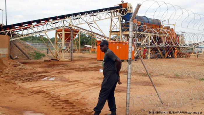 Private security employee guarding a diamond processing plant in the diamond-rich eastern Marange region, where families were expulsed from their house to make way for excavation machines of major mining companies allied to the regime of President Robert Mugabe. Marange diamonds are now part of the formal global gem trade, green-lighted by the 'blood diamond' Kimberley Process watchdog, four years after Mugabe's military ruthlessly forced out casual panners to seize control. They are now seen as key to turning around Zimbabwe's spectacular economic collapse with five companies licenced to mine what is touted as the biggest find of the last decade. AFP PHOTO / JEKESAI NJIKIZANA (Photo credit should read JEKESAI NJIKIZANA/AFP/Getty Images)