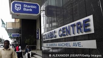 TO GO WITH AFP STORY BY Sibongile Khumalo Zimbabweans waiting in front of a South African Standard Bank branch, Stanbic Bank, in Harare on July 12, 2008. South African firms are resisting the urge to pull out of Zimbabwe despite an increasingly hostile business climate in the hope they will be in prime position to benefit from a future upturn. AFP PHOTO / Alexander Joe (Photo credit should read ALEXANDER JOE/AFP/Getty Images)