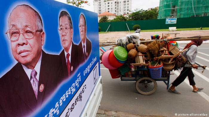 epa03797956 A Cambodian man pulls his cart, which is loaded with baskets and other household goods to sell, passing portraits of Cambodian People's Party leaders Chea Sim (L), Prime Minister Hun Sen (2-L), and President of the National Assembly Heng Samrin (3-L), in Phnom Penh, Cambodia, 23 July 2013. Cambodia's fifth national assembly elections are scheduled on 28 July. EPA/MAK REMISSA +++(c) dpa - Bildfunk+++