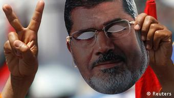A member of the Muslim Brotherhood and supporter of ousted Egyptian President Mohamed Mursi holds up a mask of Mursi while gesturing during a rally around Rabaa Adawiya square, in Cairo July 26, 2013. The Egyptian army is detaining Mursi over accusations of kidnapping, killing soldiers and other charges, the state news agency said on Friday. REUTERS/Amr Abdallah Dalsh (EGYPT - Tags: POLITICS CIVIL UNREST)