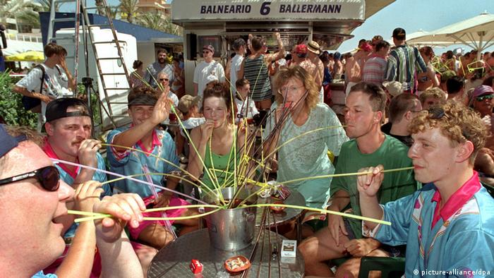People drinking from straws at Ballermann (picture-alliance/dpa)