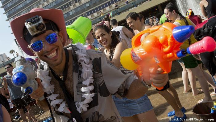 Junge Leute feiern auf einem Platz in Tel Aviv mit Wasserpistolen. (Foto: AFP PHOTO / JACK GUEZ )