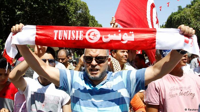 A supporter of the Islamist Ennahda movement holds up a scarf as he chants slogans during a demonstration in Tunis July 26, 2013. Several thousand Islamists took to the streets of Tunis on Friday to defend the Islamist Ennahda government against calls for it to resign in favour of a unity government after the assassination of politician Mohamed Brahmi. REUTERS/Zoubeir Souissi (TUNISIA - Tags: POLITICS CIVIL UNREST)