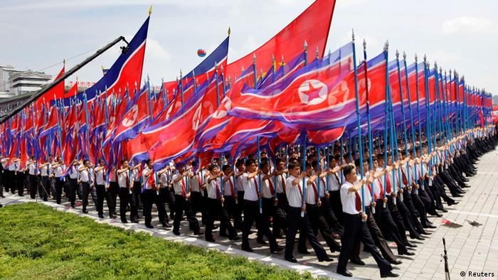 North Koreans holding national flags march during a parade to mark the 60th anniversary of the signing of a truce in the 1950-1953 Korean War at Kim Il-sung Square, in Pyongyang July 27, 2013. REUTERS/Jason Lee (NORTH KOREA - Tags: POLITICS ANNIVERSARY)