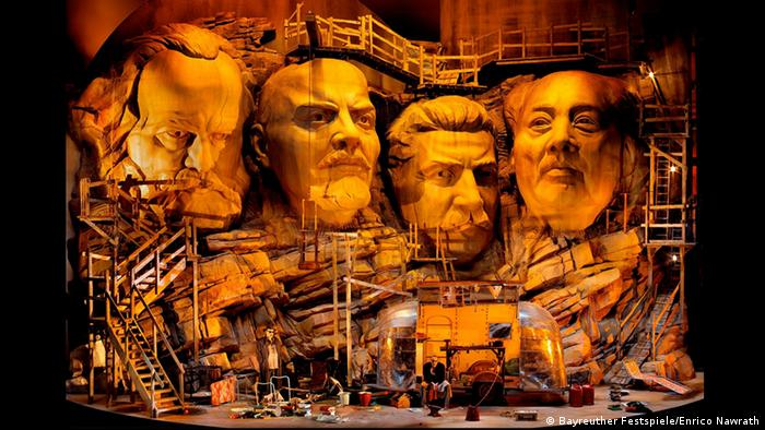 The faces of Marx, Lenin, Stalin and Mao presented in Mount Rushmore style on stage in Bayreuth