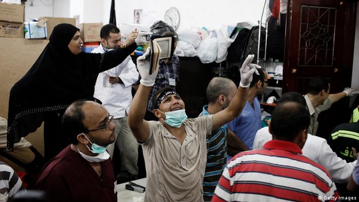 CAIRO, EGYPT - JULY 27: A supporter of deposed Egyptian President Mohammed Morsi yells inside a field hospital where bodies of supporters of Morsi are brought after reportedly being killed in fighting between pro-Morsi demonstrators and Egyptian security forces overnight, near the Rabaa al Adweya Mosque in the district of Nasr on July 27, 2013 in Cairo, Egypt. Morsi supporters had gathered at a sit in protest in Nasr City on Friday to continue demonstrations against the overthrow of Morsi, Egypt's first democratically elected leader, on July 3 by the Egyptian Armed Forces. Muslim Brotherhood leaders had called for pro-Morsi protesters to return to the streets on Friday in response to a speech made Wednesday by the Chief of Egypt's Armed Forces, General Abdel Fattah al-Sissi, who called for mass pro-military protests across Egypt on Friday against 'violence and terrorism' and in support of the military's overthrow of Morsi. (Photo by Ed Giles/Getty Images)