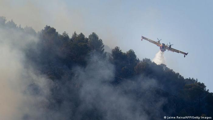 A firefighting plane drops water to extinguish a wildfire on the outskirts of Sa Coma Calenta in Andratx on the Spanish Island of Mallorca on July 26, 2013. (Photo: JAIME REINA/AFP/Getty Images)