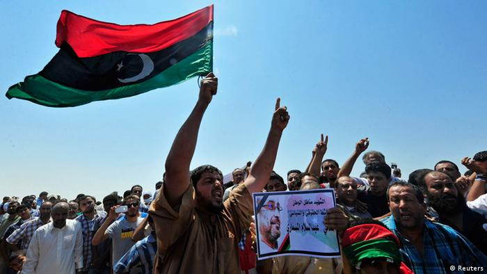 Men hold up a picture of slain lawyer and prominent Libyan political activist Abdelsalam al-Mosmary, during his funeral in Benghazi July 27, 2013. Hundreds took to the streets overnight to denounce the killing of a prominent critic of the Brotherhood, Abdelsalam al-Mosmary, who was shot dead on Friday after leaving a mosque. The words read, Martyr, activist, homeland political and human rights activist Abdul Salam Al Mosmari. REUTERS/Esam Al-Fetori (LIBYA - Tags: POLITICS CIVIL UNREST)