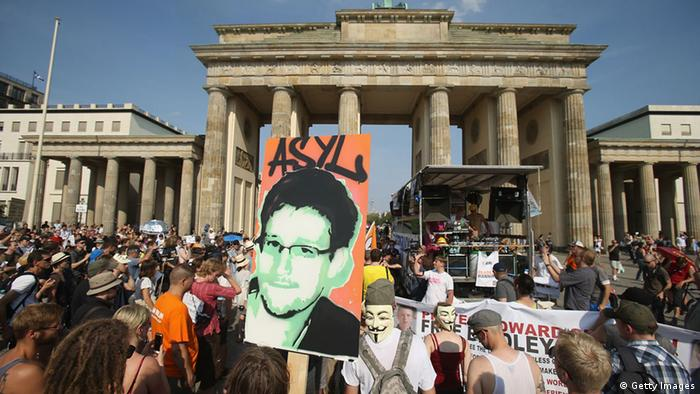 A participant holds up a picture of former NSA employee Edward Snowden with the word 'asylum' written above it at a protest gathering in front of Berlin's Brandenburg Gate against the electonic surveillance tactics of the NSA on Saturday, July 27, 2013. (Photo: Sean Gallus/Getty Images)