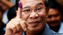 REFILE - CORRECTING COUNTRY IDENTIFIER Cambodia's Prime Minister Hun Sen shows his ink-stained finger after casting a vote in the general elections at a polling station in Kandal province July 28, 2013. REUTERS/Damir Sagolj (CAMBODIA - Tags: POLITICS ELECTIONS TPX IMAGES OF THE DAY)