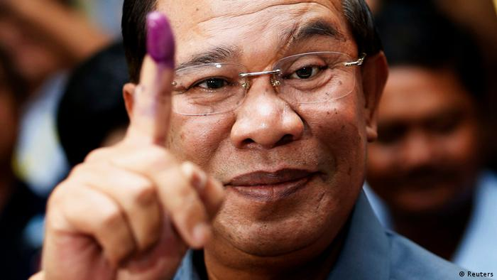 Cambodia's Prime Minister Hun Sen shows his ink-stained finger after casting a vote in the general elections at a polling station in Kandal province July 28, 2013 (Photo: REUTERS/Damir Sagolj)