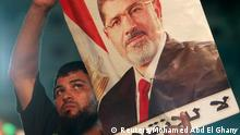A supporter of deposed Egyptian President Mohamed Mursi carries a Mursi poster during a protest at the Rabaa Adawiya square, where Mursi supporters are camping, in Cairo July 27, 2013. At least 70 people died on Saturday after security forces attacked supporters of deposed President Mohamed Mursi in Cairo, Muslim Brotherhood spokesman Gehad El-Haddad said, adding the toll could be much higher. REUTERS/Mohamed Abd El Ghany (EGYPT - Tags: POLITICS CIVIL UNREST)