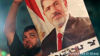 Mursijev pristaša drži plakat s Mursijevom fotografijom