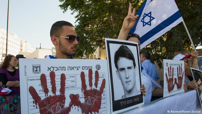 An Israeli holds a picture of a victim of a militant attack during a protest outside the office of Israel's Prime Minister Benjamin Netanyahu in Jerusalem, against the release of Arab prisoners as a step to renew stalled peace talks with the Palestinians, July 28, 2013. Netanyahu on Sunday urged divided rightists in his cabinet to approve the release of 104 Arab prisoners in order to restart peace talk with the Palestinians. REUTERS/Ronen Zvulun (JERUSALEM - Tags: POLITICS CIVIL UNREST)