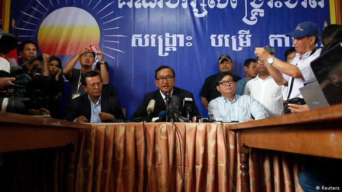 Sam Rainsy (C), president of the Cambodia National Rescue Party (CNRP) addresses reporters at his party's headquarters in Phnom Penh July 29, 2013. REUTERS/Samrang Pring (CAMBODIA - Tags: POLITICS ELECTIONS)