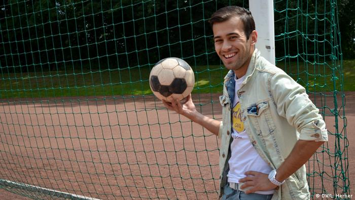 Soccer player Süleyman, who plays for Arminia Hassel in Gelsenkirchen, standing in front of a goal with a soccer ball in his hand