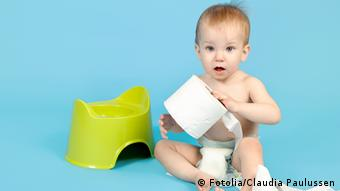 A baby sits next to a potty, grasping a roll of toilet paper in her hands