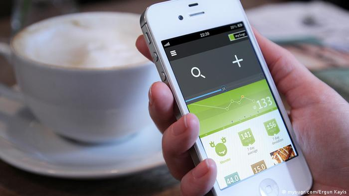 Image of a coffee cup and a hand holding a smartphone that's running the app mySugr (Photo: mySugr)
