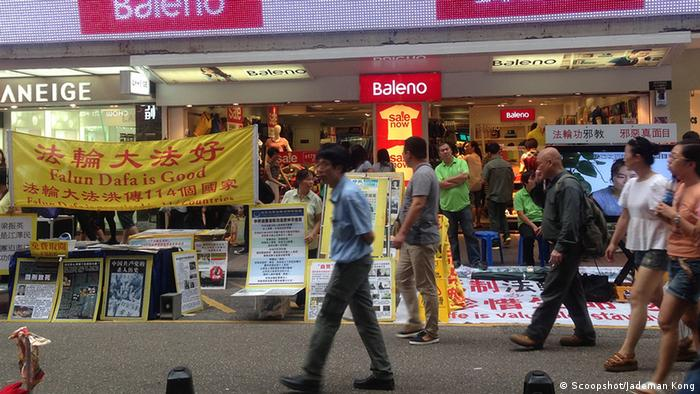 Falun Dafa is black listed by the China government as an illegal religion. However they are still active in Hong Kong because there is religion freedom here. At the same time many people in Hong Kong think that Falun Dafa is evil. In this photo, the left booth Falun Dafa members are promoting their organization. Just next to them, the right booth is the anti Falun Dafa organization who discloses the evil side of Falun Dafa. Aufnahmedatum: 2013-07-13 12:07 5-19 Sai Yeung Choi Street South, Mong Kok, Hong Kong Credit: Scoopshot / Jademan Kong