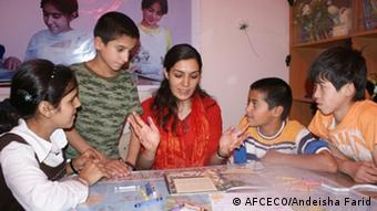 Andeisha Farid sits at a table with children and teaches lessons from textbooks. Copyright: AFCECO