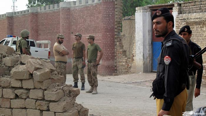 Policemen (R) and Ranger soldiers (L) stand outside a prison following a Taliban attack in Dera Ismail Khan July 30, 2013 (Photo: REUTERS/Stringer)