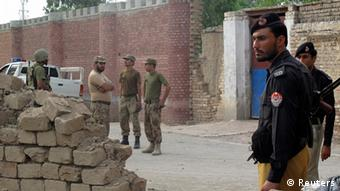 Policemen (R) and Ranger soldiers (L) stand outside a prison following a Taliban attack in Dera Ismail Khan July 30, 2013. (Photo: Reuters)