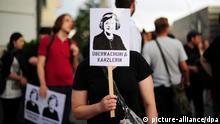 Eine Demonstrantin hält am 29.07.2013 in Berlin während eines Protest-Spaziergangs vor dem Neubau des Bundesnachrichtendienstes (BND) gegen Überwachung ein Plakat mit der Aufschrift Überwachungskanzlerin hoch. Zu der Demo hatten Netz-Aktivisten der Digitalen Gesellschaft aufgerufen. Foto: Daniel Reinhardt/dpa