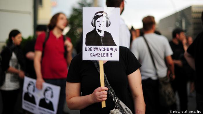 A pro-privacy protestor holds a sign at a rally in Berlin