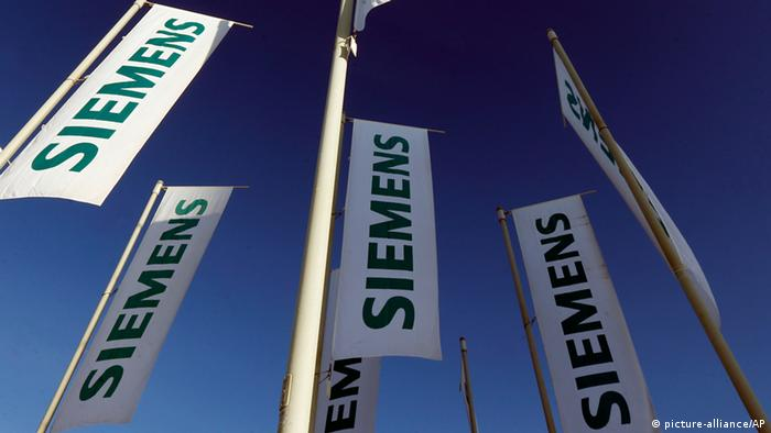 Flags of German engineering conglomerate Siemens AG flutter before the annual shareholder meeting in Munich, southern Germany, on Wednesday, Jan. 23, 2013. Siemens AG said its net earnings declined 12 percent in the October-December quarter as revenue edged slightly higher, new orders declined and the company took one-time charges — some related to the solar power business it is selling. (AP Photo/Matthias Schrader)